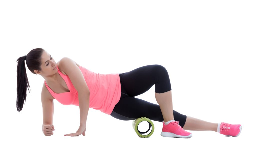 Woman practicing relaxation with a hollow foam roller